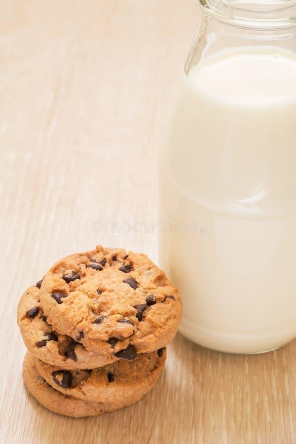 Galletas de microprocesador de chocolate con la botella de leche imagen de archivo libre de regalías