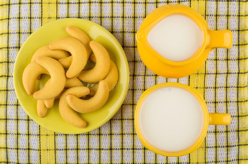 Galletas de torta dulce en platillo, leche del jarro y taza amarilla fotografía de archivo libre de regalías