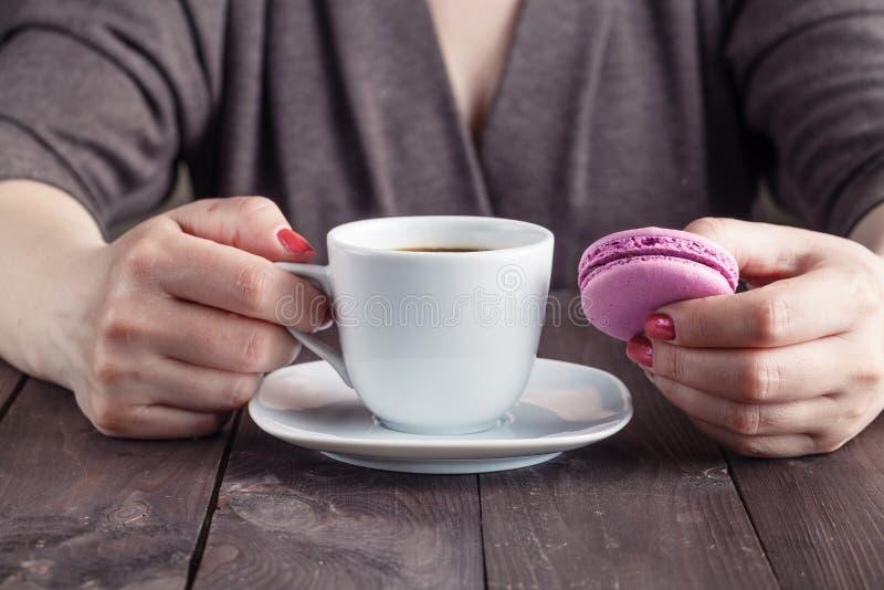 Galletas del café y del macaron en la tabla por la mañana, mano femenina imagen de archivo