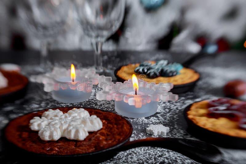 Galletas del chocolate de la Navidad con nuevo Year& x27; decoraciones festivas de una vela de s en la tabla foto de archivo