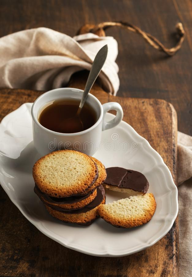 Galletas del chocolate en la placa con la taza de té en fondo rústico fotos de archivo