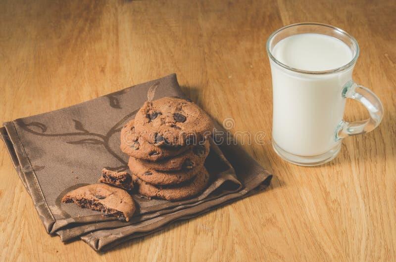 Galletas del chocolate y vidrio de leche/de galletas del chocolate y vidrio de fondo de madera de la leche Foco selectivo imagen de archivo libre de regalías