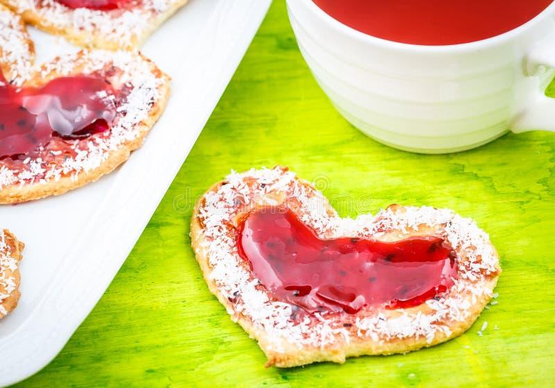 Galletas del corazón con el atasco y el té imagenes de archivo