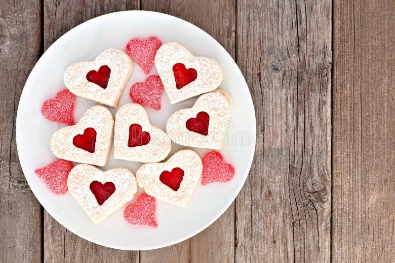 Galletas del corazón del día de tarjetas del día de San Valentín con el atasco y los caramelos sobre la madera imagen de archivo libre de regalías