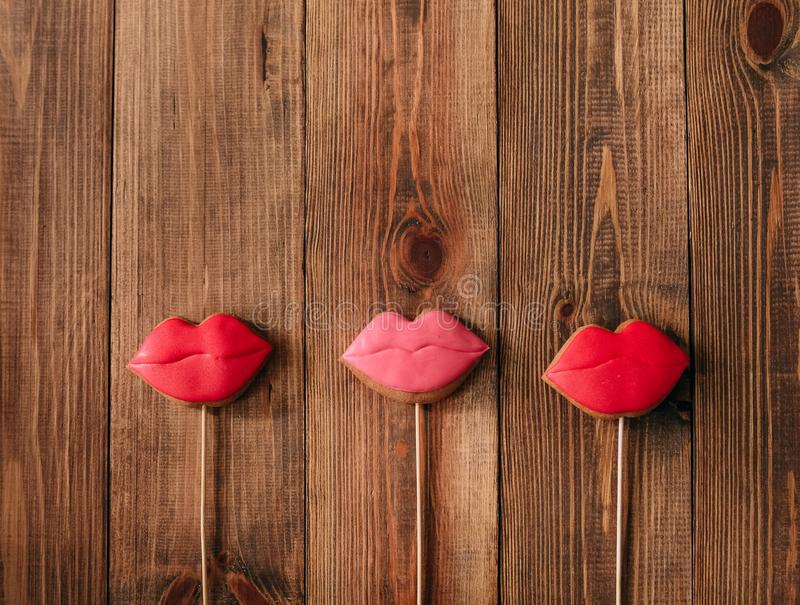 Galletas del día de fiesta que hielan el pan de jengibre rojo del palillo de los labios fotos de archivo