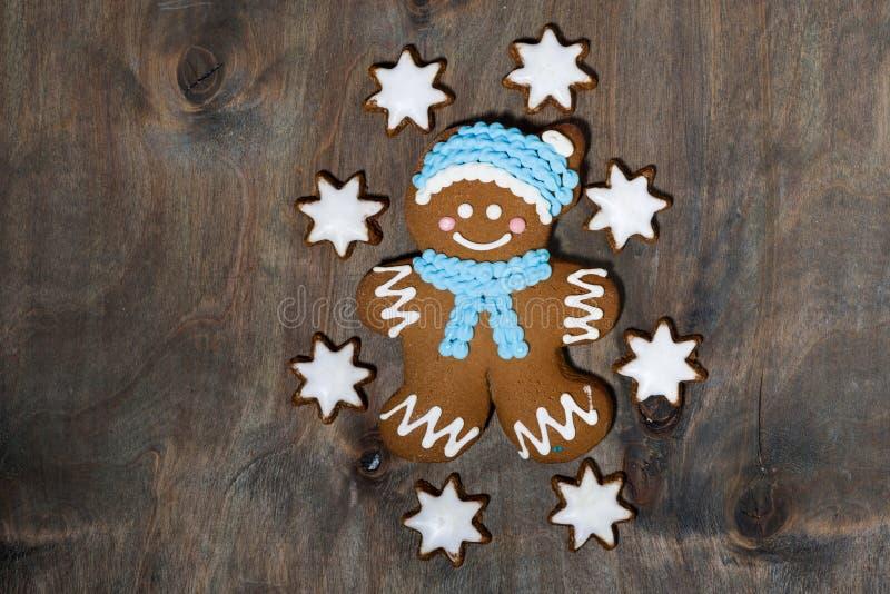 galletas del hombre de pan de jengibre y de las estrellas en fondo de madera gris fotos de archivo