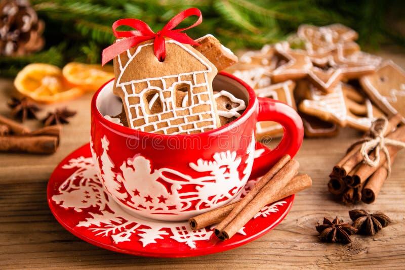 Galletas del jengibre de la Navidad en una taza roja fotografía de archivo libre de regalías