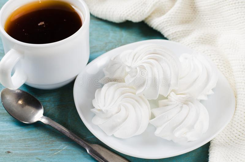 Galletas del merengue y taza deliciosas de té caliente fotografía de archivo