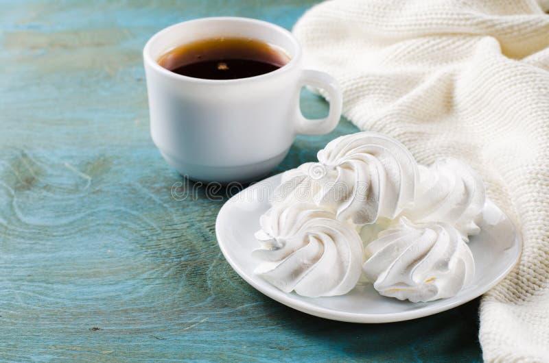 Galletas del merengue y taza deliciosas de té caliente foto de archivo