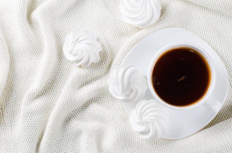 Galletas del merengue y taza deliciosas de té caliente foto de archivo libre de regalías