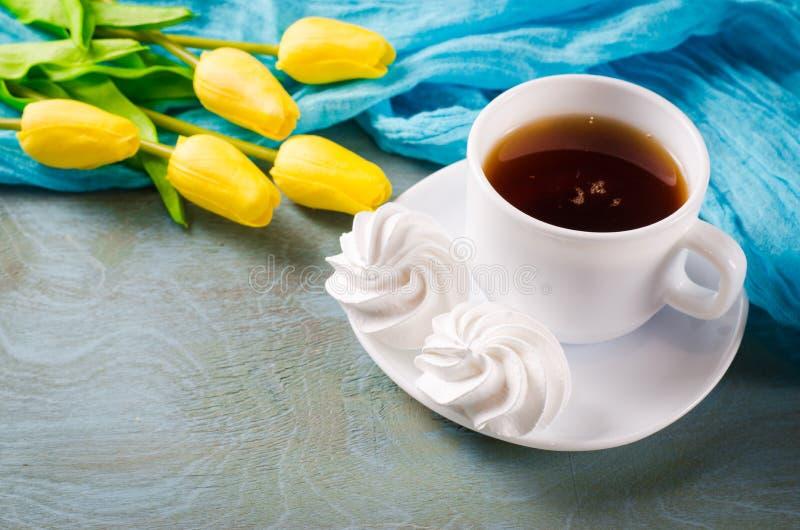 Galletas del merengue y taza deliciosas de té caliente fotos de archivo