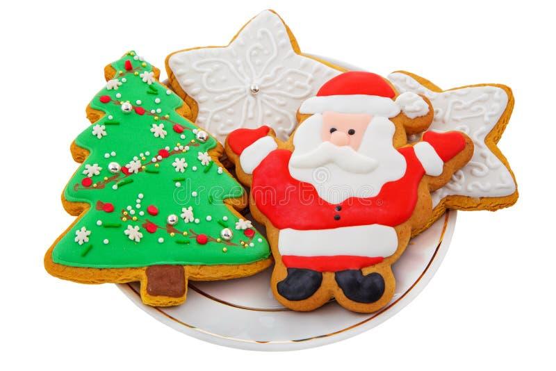 Galletas del pan de jengibre de la Navidad en una placa blanca foto de archivo