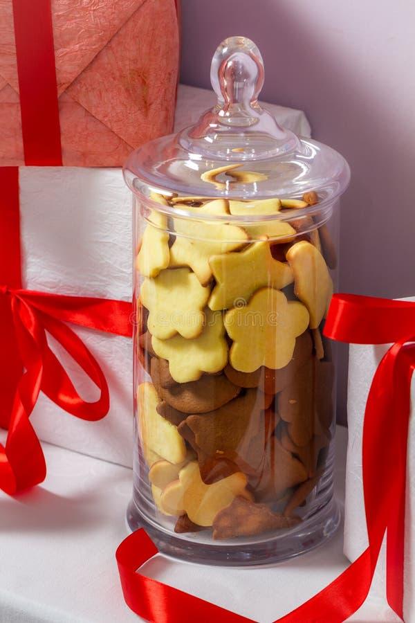 Galletas del pan de jengibre en un tarro y regalos de la Navidad foto de archivo