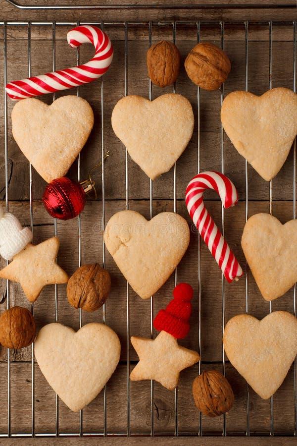 Galletas del pan de jengibre de la Navidad con la decoración festiva en el fondo de madera de la bandeja y del vintage, primer rú imagen de archivo