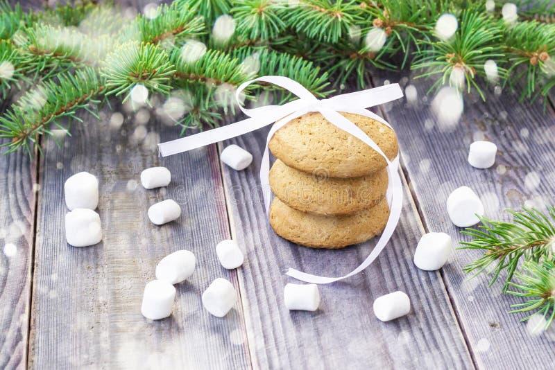Galletas del pan de jengibre de la Navidad con las decoraciones y melcochas en fondo con el árbol de navidad adornado con nieve fotos de archivo