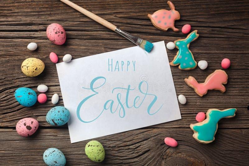Galletas del pan de jengibre de Pascua en la tabla de madera Conejos y huevos Tarjeta de felicitaci?n fotos de archivo libres de regalías