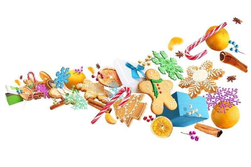 Galletas del pan de jengibre y decoraciones de la Navidad presentadas en el aire aislado en el fondo blanco imagen de archivo libre de regalías