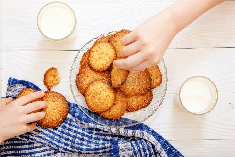 Galletas del s?samo con la leche para el desayuno para los ni?os Manos del ` s de los ni?os en el marco Los ni?os comen las galle foto de archivo libre de regalías