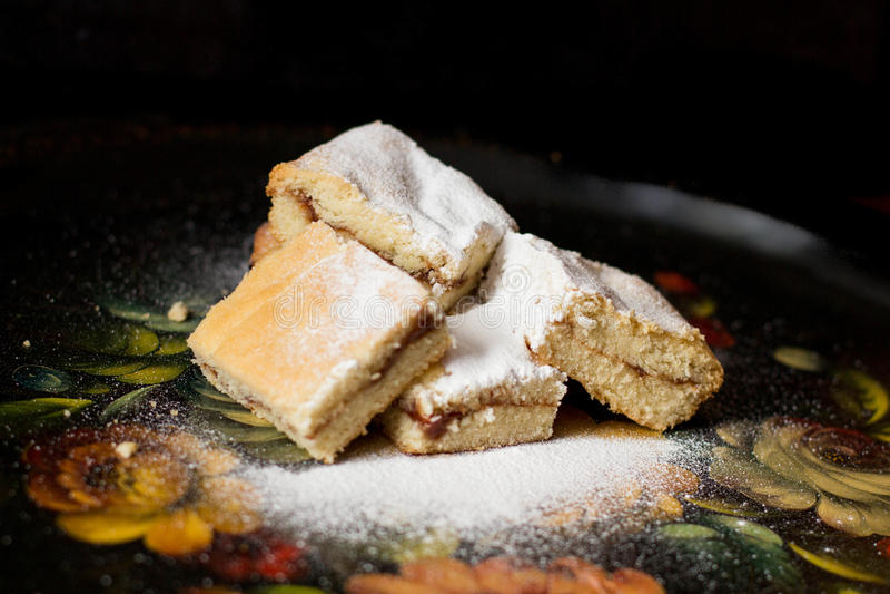 Galletas dulces hechas en casa con el atasco, asperjado con el azúcar en polvo, cierre para arriba fotografía de archivo