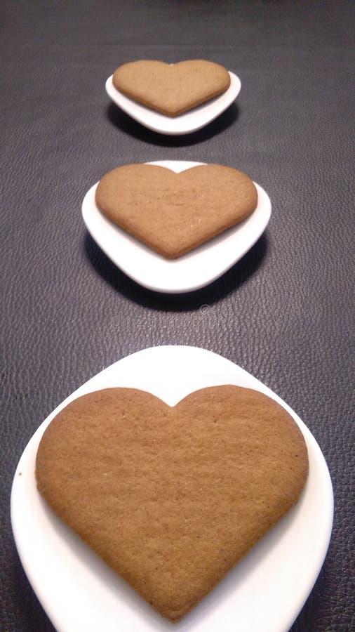 Galletas en forma de corazón en los platillos Rhombus-formados blancos fotos de archivo