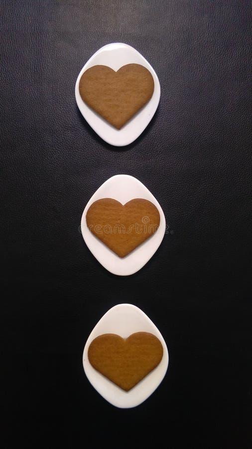 Galletas en forma de corazón en los platillos Rhombus-formados blancos y el fondo negro fotografía de archivo