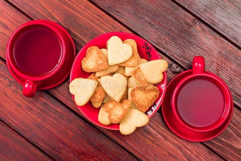 Galletas en forma de corazón y dos tazas de té en tazas rojas brillantes en una sobremesa de madera teñida imagenes de archivo
