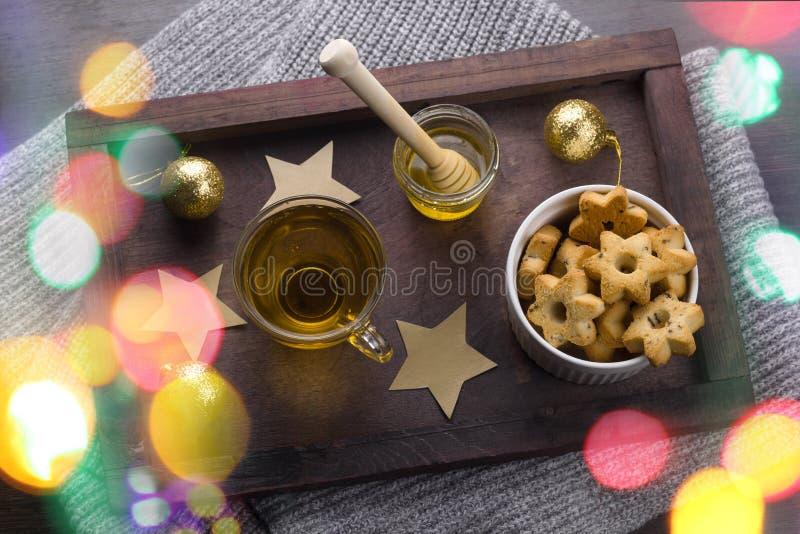 Galletas en una forma de estrellas, de la taza de té, del tarro de la miel y de las bolas de oro de la Navidad fotografía de archivo libre de regalías