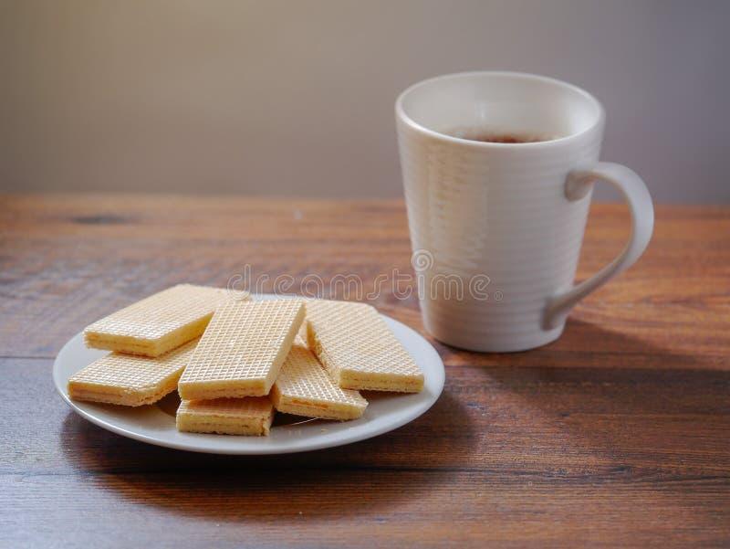 Galletas en una placa blanca y una taza de té caliente en una tabla de madera Concepto del desayuno imagenes de archivo