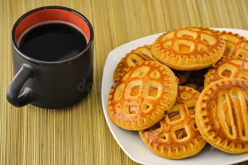 Galletas en una placa y una taza de café en una taza negra Visión desde arriba fotos de archivo libres de regalías