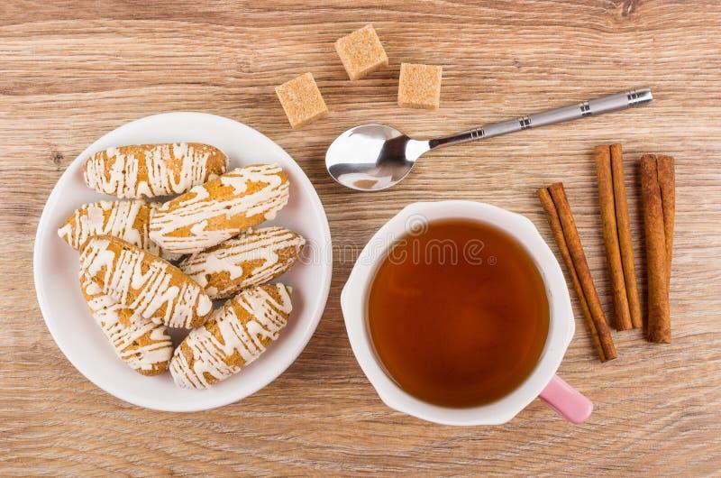 Galletas esmaltadas en el platillo, azúcar, palillos de canela, cuchara, té fotografía de archivo libre de regalías