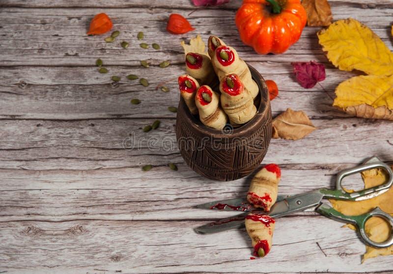 Galletas espeluznantes y sabrosas 'dedo de bruja', tijeras en la sangre, hojas de otoño, fisalis y calabaza sobre un fondo de mad imagen de archivo libre de regalías