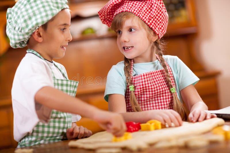 Galletas felices sonrientes del makin de los niños en cocina imagen de archivo libre de regalías