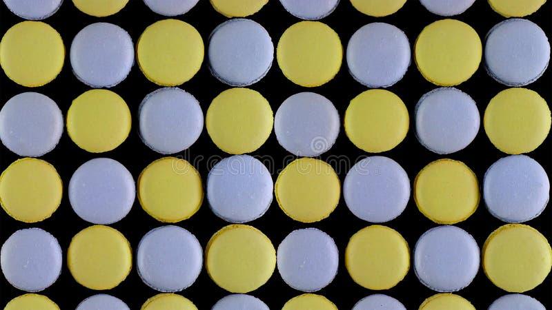 Galletas francesas coloridas dulces de los macarrones en el fondo oscuro, visión superior imagenes de archivo
