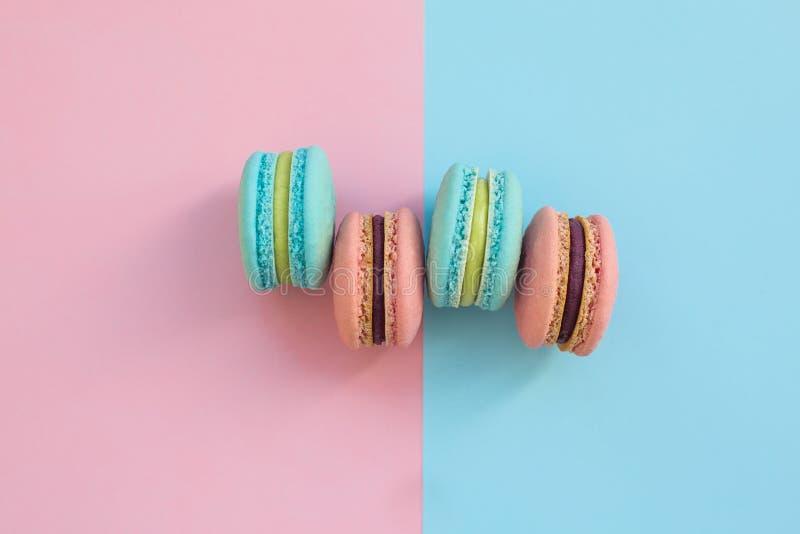 Galletas francesas coloridas dulces de los macarrones en el rosa y el fondo en colores pastel azul, visión superior Injurie la se fotos de archivo