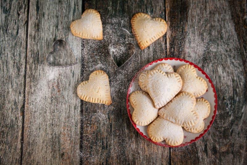 Galletas hechas en casa de la forma del corazón con crema de las natillas de la vainilla imagenes de archivo