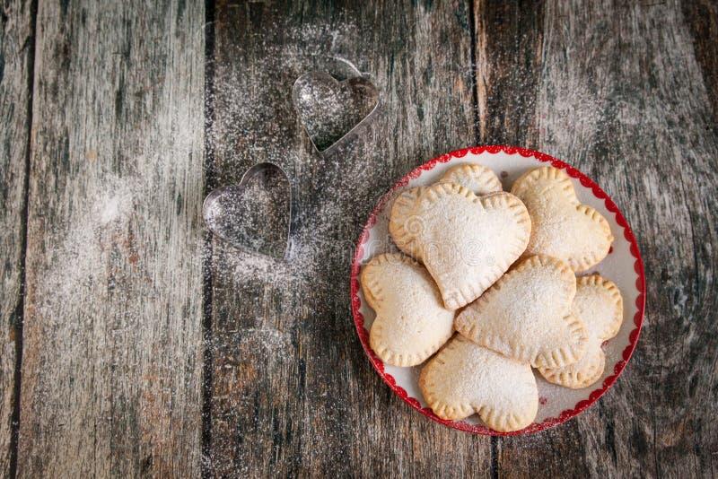 Galletas hechas en casa de la forma del corazón con crema de las natillas de la vainilla foto de archivo