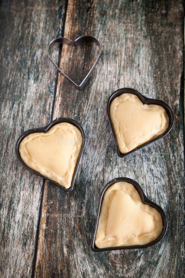 Galletas hechas en casa de la forma del corazón con crema de las natillas de la vainilla fotos de archivo