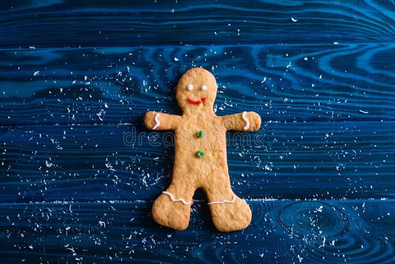 Galletas hechas en casa de la Navidad del primer en la forma de hombre de pan de jengibre en la tabla de la marina de guerra foto de archivo