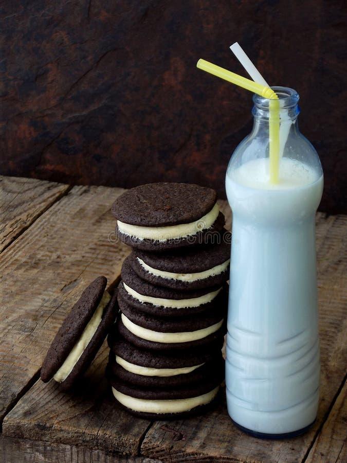 Galletas hechas en casa del chocolate con la crema de la melcocha y el botle blancos de la leche en fondo oscuro Foco selectivo foto de archivo