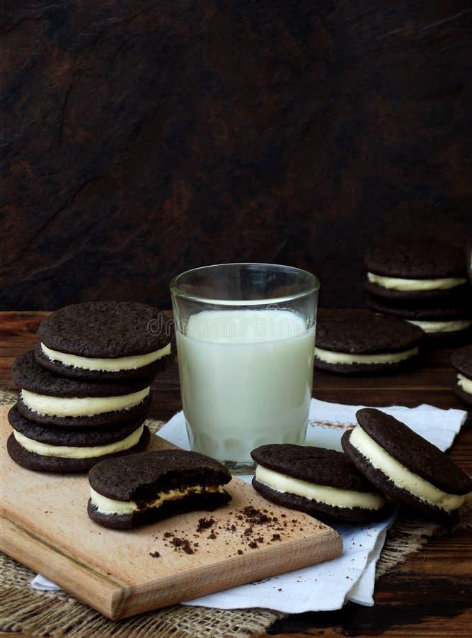 Galletas hechas en casa del chocolate de Oreo con la crema de la melcocha y el vidrio blancos de leche en fondo oscuro Foco selec fotos de archivo libres de regalías