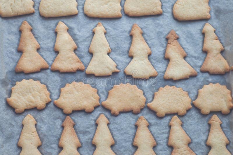 Galletas hechas en casa en la forma del conejo, árbol de navidad, erizo en una cacerola apenas del horno en el pergamino Otoño e  imagenes de archivo