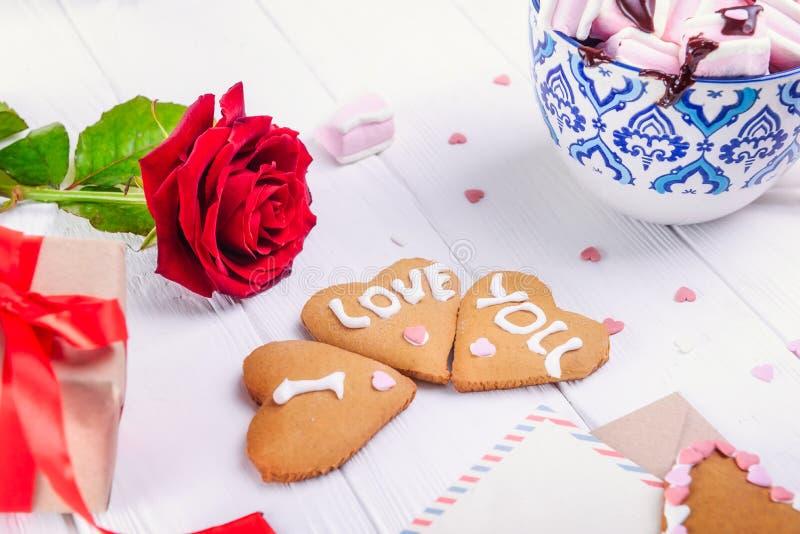 Galletas hechas en casa en la forma del corazón con te amo palabras en la tabla de madera blanca con la tarjeta de felicitación,  imagenes de archivo