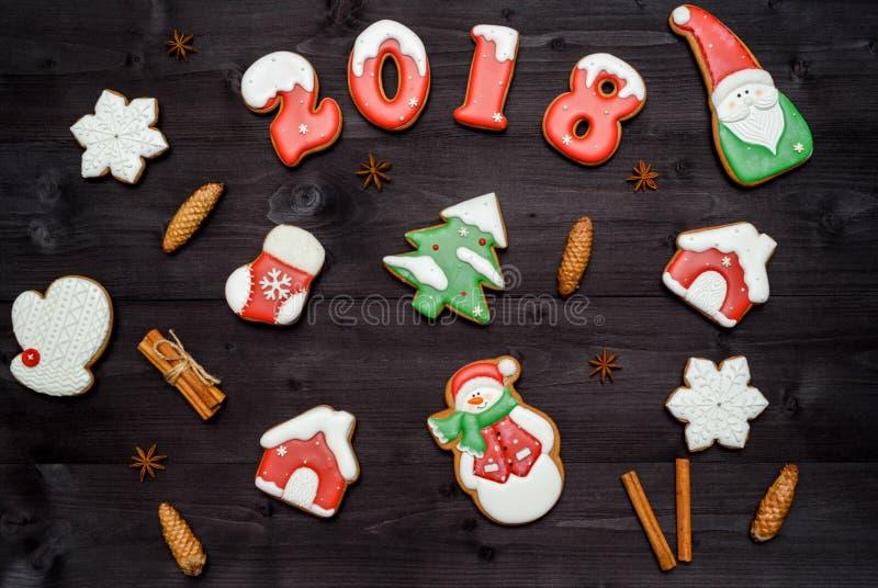 Galletas hechas en casa sabrosas del pan de jengibre de la Navidad en la tabla de madera, visión superior El Año Nuevo 2018 coció imagen de archivo