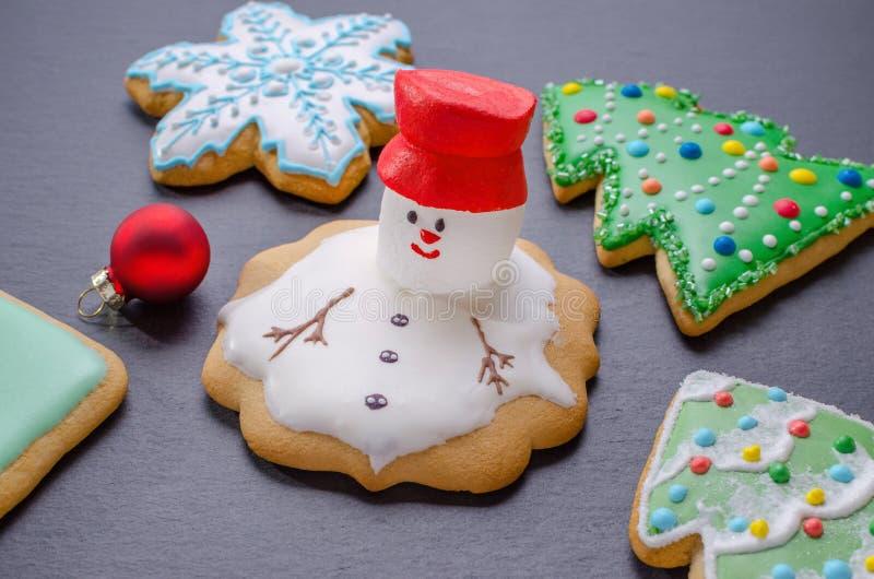 Galletas hechas a mano de la Navidad, muñeco de nieve derretido con la choza roja foto de archivo
