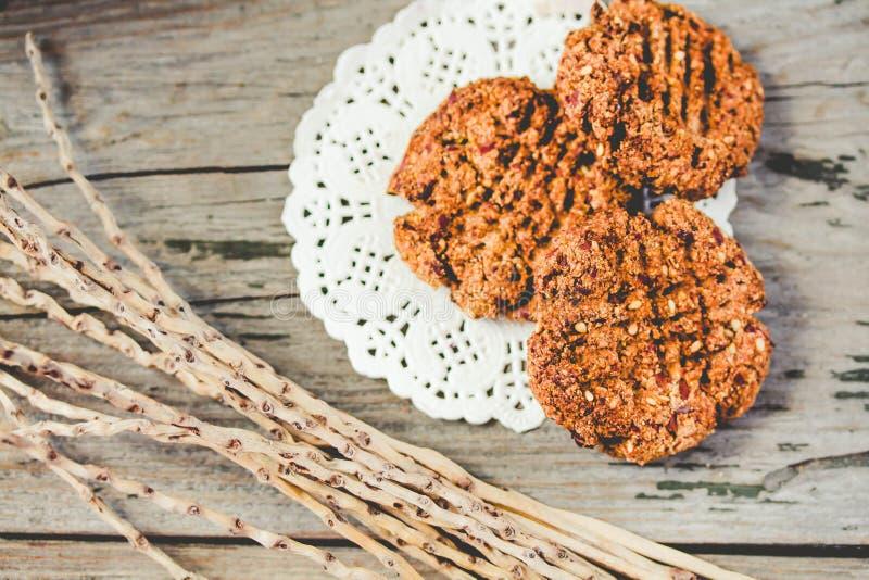 Galletas integrales hechas en casa con las semillas de la harina de avena, de lin y de s?samo en la tabla de madera r?stica Galle imagen de archivo