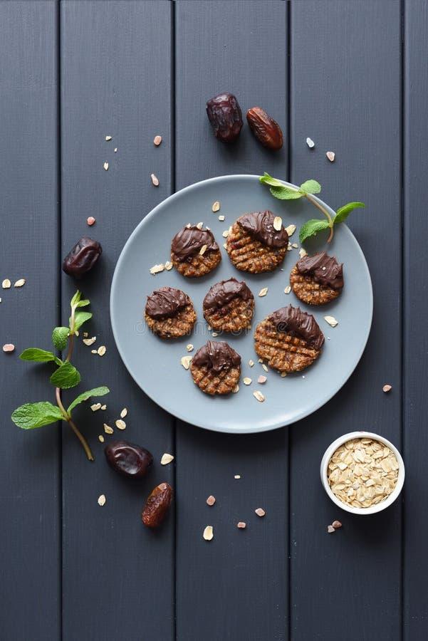 Galletas libres del estilo del paleo del gluten crudo del vegano con el chocolate derretido y la sal himalayan en la placa gris fotografía de archivo
