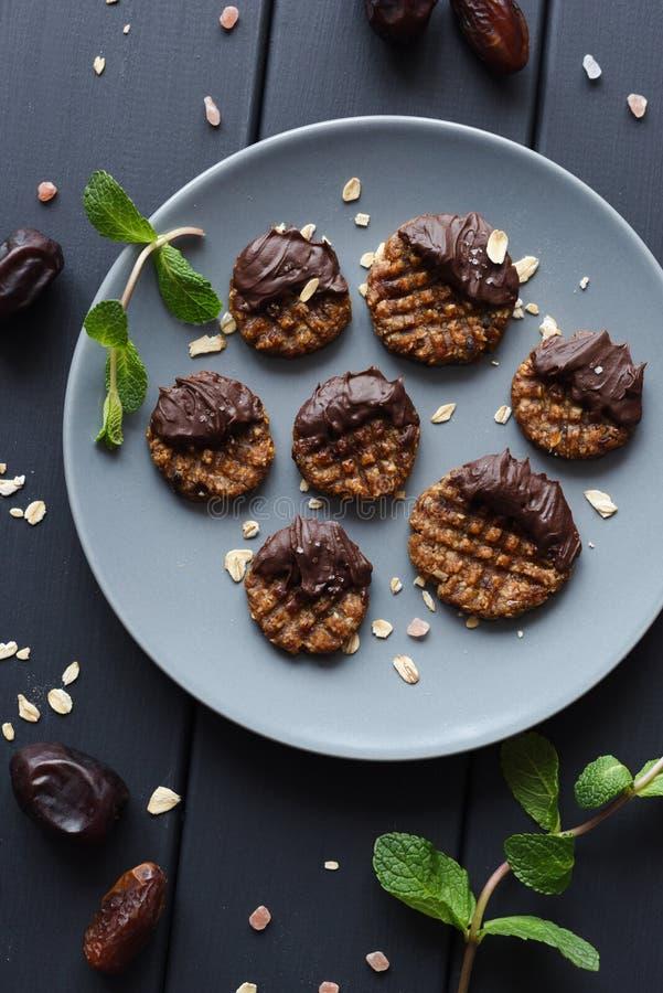 Galletas libres del estilo del paleo del gluten crudo del vegano con el chocolate derretido y la sal himalayan en la placa gris imagen de archivo