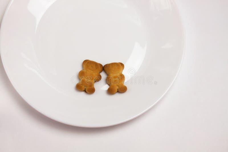Galletas lindas de los osos en la placa redonda de cer?mica en el fondo blanco Visi?n desde arriba, endecha plana fotografía de archivo