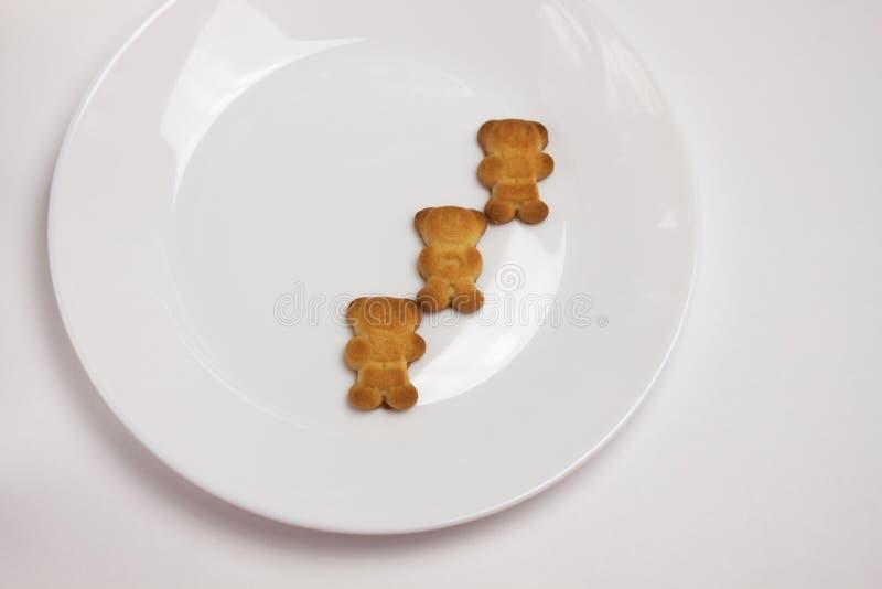 Galletas lindas de los osos en la placa redonda de cer?mica en el fondo blanco Visi?n desde arriba, endecha plana imagen de archivo libre de regalías
