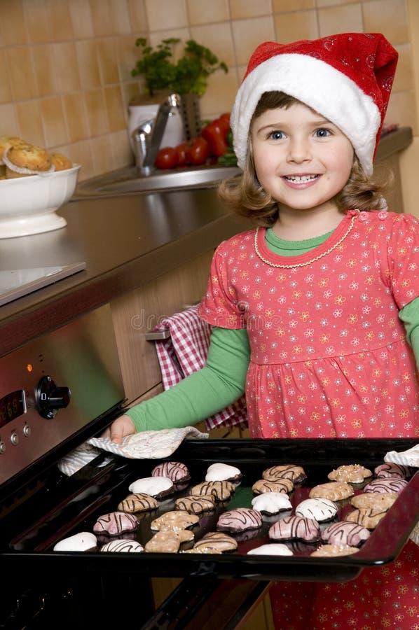 Galletas lindas de Navidad de la hornada de la muchacha imagen de archivo